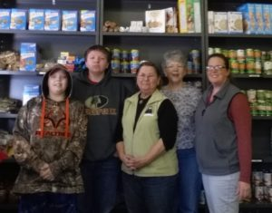 Volunteers standing together in front of the food pantry shelving.