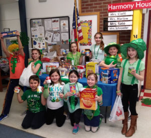 Students holding non-perishable items donated at the Lucky Day Carnival.